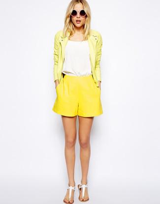Cómo combinar: sandalias de dedo de cuero blancas, pantalones cortos amarillos, camiseta sin manga blanca, chaqueta motera de cuero amarilla