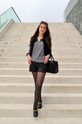 Cómo combinar: botines de cuero con adornos negros, pantalones cortos de cuero negros, jersey de pico gris, cazadora de aviador de cuero negra