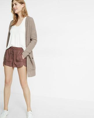 Cómo combinar: tenis blancos, pantalones cortos marrónes, camiseta sin manga blanca, cárdigan abierto de punto en beige