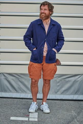 Outfits hombres: Empareja un blazer de lino azul marino con unos pantalones cortos naranjas para lograr un look de vestir pero no muy formal. ¿Quieres elegir un zapato informal? Elige un par de tenis de cuero blancos para el día.