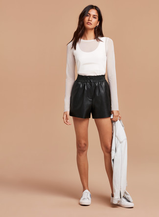 Cómo combinar: tenis blancos, pantalones cortos de cuero negros, camiseta de manga larga de malla blanca, chaqueta vaquera blanca