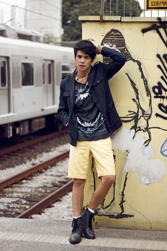 Cómo combinar: botas brogue de cuero negras, pantalones cortos amarillos, sudadera estampada en negro y blanco, chaqueta campo negra