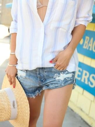 Cómo combinar: sombrero de paja marrón claro, pantalones cortos vaqueros desgastados azules, top de bikini de crochet en beige, camisa de vestir de rayas verticales en blanco y azul