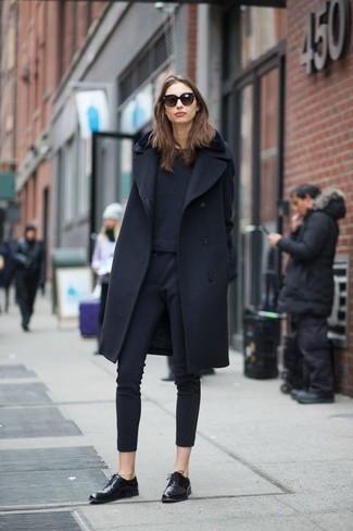 Cómo combinar: zapatos oxford de cuero negros, pantalones pitillo azul marino, jersey con cuello circular azul marino, abrigo negro