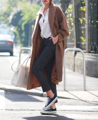 Cómo combinar: tenis de lona en negro y blanco, pantalones pitillo de rayas verticales en negro y blanco, blusa de botones blanca, abrigo marrón
