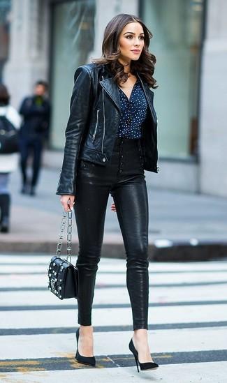 Cómo combinar: zapatos de tacón de ante negros, pantalones pitillo de cuero negros, blusa de botones a lunares en azul marino y blanco, chaqueta motera de cuero negra