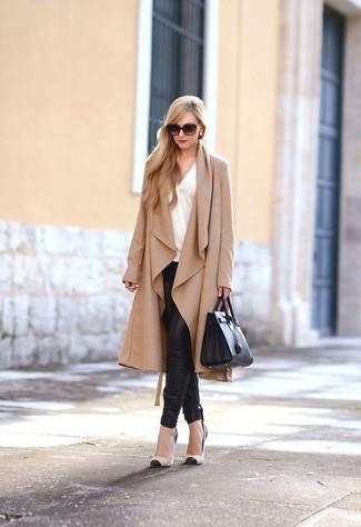 Cómo combinar: zapatos de tacón de cuero en negro y marrón claro, pantalones pitillo de cuero negros, blusa de manga larga blanca, abrigo duster marrón claro