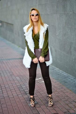 Cómo combinar: sandalias de tacón de cuero con print de serpiente grises, pantalones pitillo negros, blusa de manga larga verde oliva, chaleco de pelo blanco