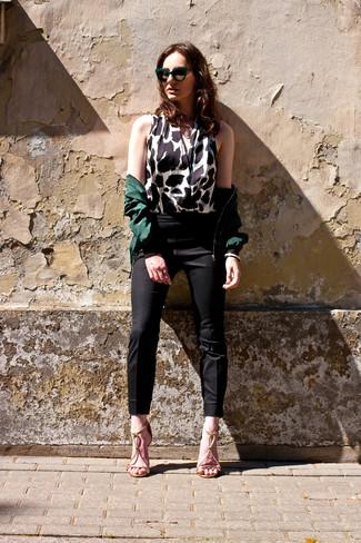 Cómo combinar: sandalias de tacón de cuero doradas, pantalones pitillo negros, blusa sin mangas de leopardo en blanco y negro, cazadora de aviador verde oscuro