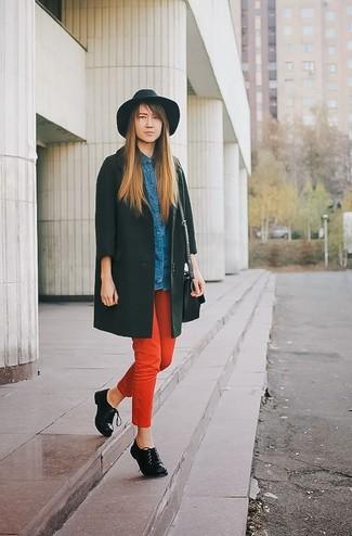 Cómo combinar: zapatos oxford de cuero negros, pantalones pitillo rojos, camisa vaquera azul, abrigo verde oscuro