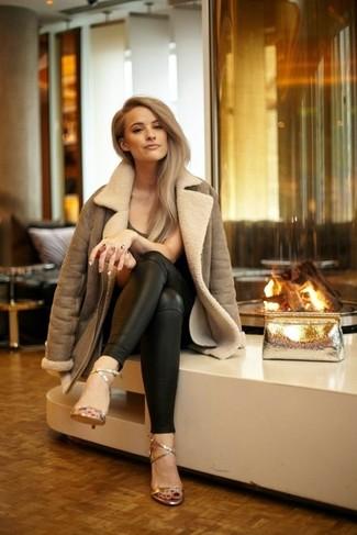Cómo combinar: sandalias de tacón de cuero doradas, pantalones pitillo de cuero negros, camiseta con cuello circular en marrón oscuro, chaqueta de piel de oveja marrón