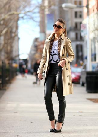 Cómo combinar: zapatos de tacón de cuero negros, pantalones pitillo de cuero negros, camiseta con cuello circular estampada en blanco y negro, gabardina marrón claro