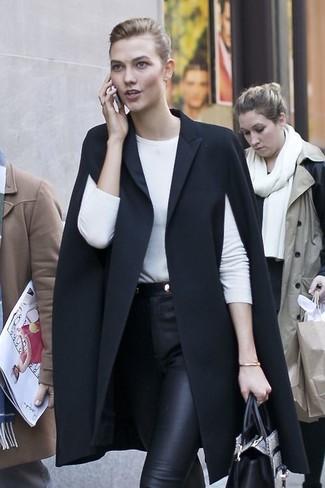 Combinar una bolsa tote de cuero con print de serpiente gris: Utiliza una capa negra y una bolsa tote de cuero con print de serpiente gris para un look agradable de fin de semana.