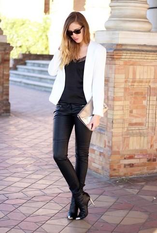Cómo combinar: botines de cuero negros, pantalones pitillo negros, camiseta sin manga de seda negra, blazer blanco