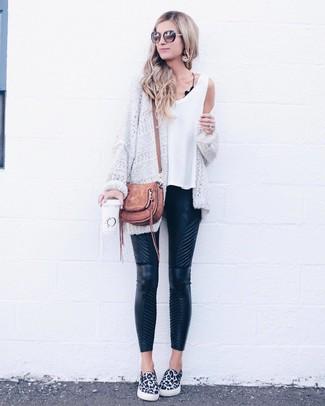 Cómo combinar: zapatillas slip-on de leopardo en blanco y negro, pantalones pitillo de cuero acolchados negros, camiseta sin manga blanca, cárdigan abierto de punto blanco
