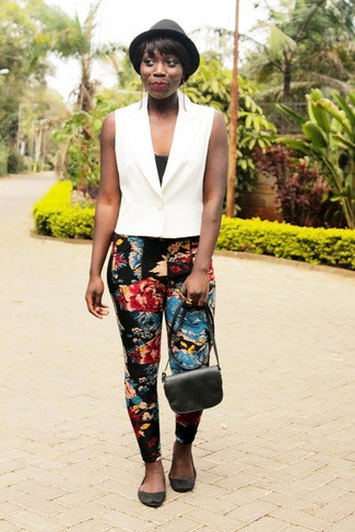 Cómo combinar: bailarinas de ante negras, pantalones pitillo con print de flores negros, camiseta sin manga negra, chaleco blanco