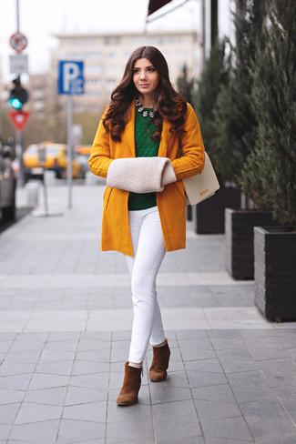 Cómo combinar: botines de ante marrónes, pantalones pitillo blancos, jersey con cuello circular verde oscuro, abrigo mostaza