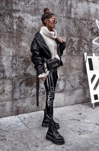Cómo combinar: botas planas con cordones de cuero gruesas negras, pantalones pitillo de cuero negros, jersey de cuello alto de lana de punto blanco, cazadora de aviador de cuero negra