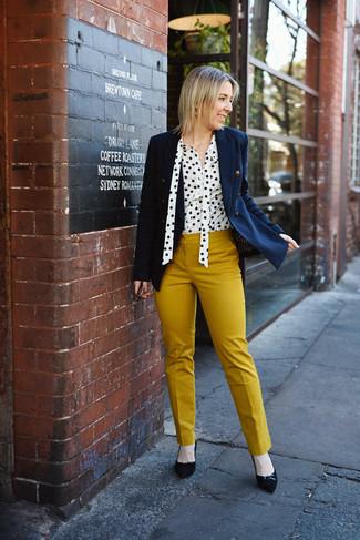 Cómo combinar: zapatos de tacón de ante negros, pantalones pitillo mostaza, blusa de botones a lunares en blanco y negro, blazer cruzado azul marino