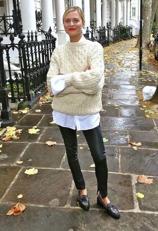 Cómo combinar: mocasín de cuero con tachuelas negros, pantalones pitillo de cuero negros, camisa de vestir blanca, jersey oversized de punto en beige