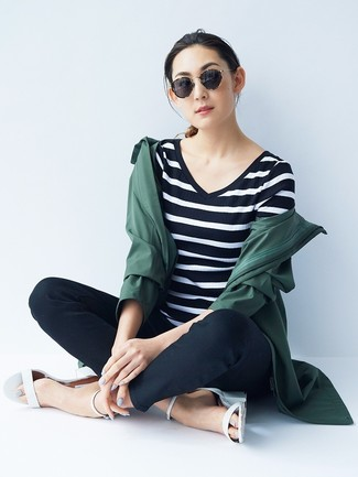 Cómo combinar: sandalias de tacón de cuero blancas, pantalones pitillo negros, camiseta con cuello en v de rayas horizontales en negro y blanco, chubasquero verde oscuro