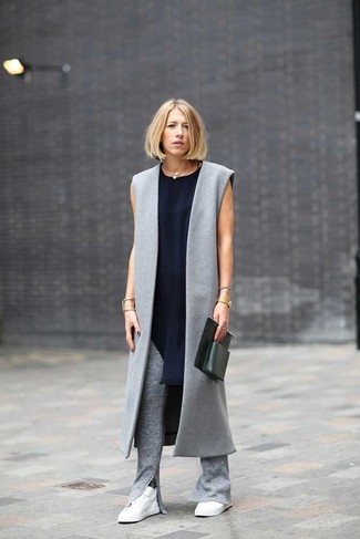 Cómo combinar: tenis blancos, pantalones pitillo de punto grises, túnica de seda azul marino, abrigo sin mangas gris