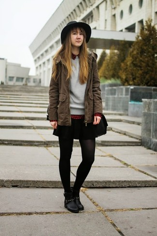 Muestra tu lado lúdico con una parka marrón y una falda skater negra. Con el calzado, sé más clásico y opta por un par de botines de cuero negros.