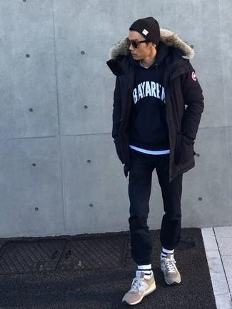 Cómo combinar: parka negra, sudadera con capucha estampada azul marino, camiseta con cuello circular celeste, pantalón chino negro