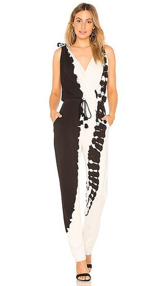 Cómo combinar: pendientes dorados, sandalias de tacón de ante negras, mono efecto teñido anudado en negro y blanco