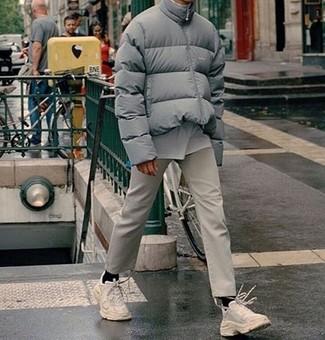 Un plumífero gris y un pantalón chino beige son un look perfecto para ir a la moda y a la vez clásica. Para el calzado ve por el camino informal con deportivas blancas.