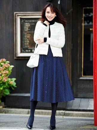 Cómo combinar: plumífero blanco, jersey de cuello alto negro, falda midi a lunares azul marino, zapatos de tacón de cuero negros
