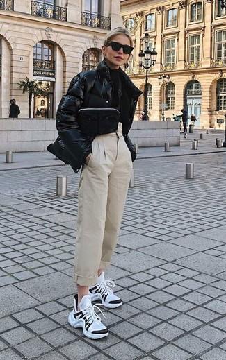 Cómo combinar: plumífero negro, jersey de cuello alto negro, pantalón de pinzas en beige, deportivas en blanco y negro