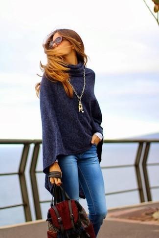 Cómo combinar: poncho azul marino, vaqueros pitillo azules, mochila roja, colgante dorado