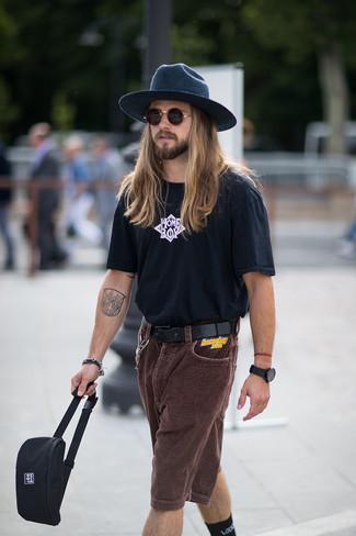 Cómo combinar: sombrero de lana azul marino, riñonera de lona negra, pantalones cortos de pana en marrón oscuro, camiseta con cuello circular estampada en negro y blanco