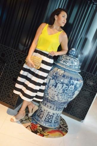 Cómo combinar: cartera sobre de paja marrón claro, sandalias con cuña de cuero en beige, falda midi de rayas horizontales en blanco y negro, blusa sin mangas amarilla