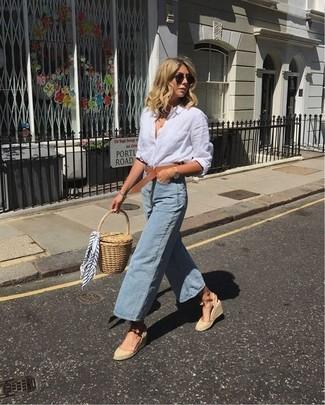 Cómo combinar: cartera sobre de paja marrón claro, sandalias con cuña de lona en beige, falda pantalón vaquera celeste, camisa de vestir de lino blanca