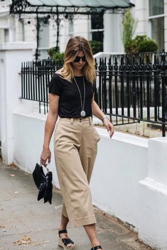 Cómo combinar: cartera sobre de cuero negra, sandalias con cuña de cuero negras, falda pantalón en beige, camiseta con cuello circular negra