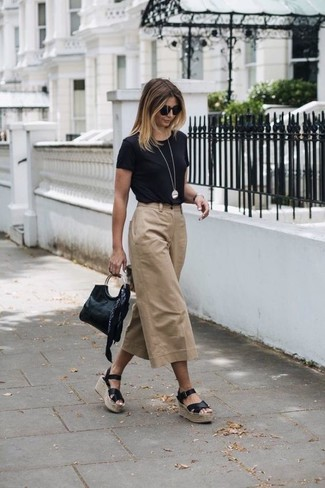 Cómo combinar: cartera sobre de cuero negra, sandalias con cuña de cuero negras, falda pantalón marrón claro, camiseta con cuello circular negra