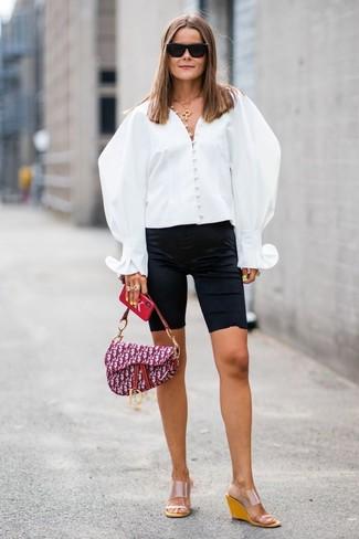 Cómo combinar: bolso de hombre de lona estampado morado, sandalias con cuña de goma transparentes, mallas ciclistas negras, blusa de botones blanca