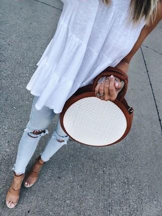 Cómo combinar: bolso bandolera de paja blanco, sandalias con cuña de cuero marrón claro, vaqueros pitillo desgastados celestes, blusa sin mangas blanca
