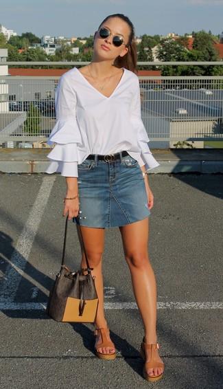 Cómo combinar: mochila con cordón de cuero en marrón oscuro, sandalias con cuña de cuero marrón claro, minifalda vaquera azul, blusa de manga larga con volante blanca