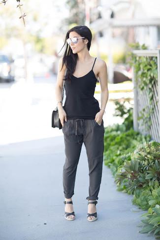 Cómo combinar: bolso bandolera de cuero negro, sandalias con cuña de cuero negras, pantalón de pinzas en gris oscuro, camiseta sin manga negra