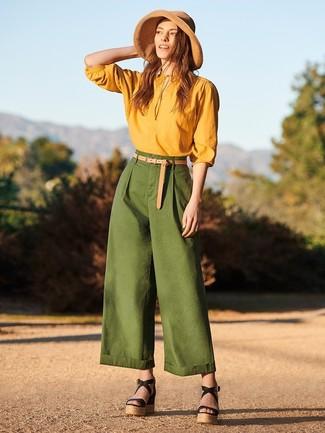 Combinar unos pantalones anchos verde oscuro: Emparejar una blusa de manga larga mostaza con unos pantalones anchos verde oscuro es una opción práctica para un día en la oficina. Sandalias con cuña de cuero negras contrastarán muy bien con el resto del conjunto.