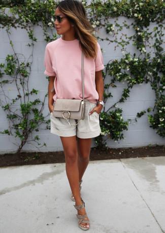 Cómo combinar: bolso bandolera de cuero gris, sandalias con cuña de ante grises, pantalones cortos de lino grises, camiseta con cuello circular rosada