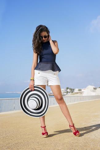 Cómo combinar: sombrero de paja en blanco y negro, sandalias con cuña de ante rojas, pantalones cortos blancos, top con sobrefalda azul marino