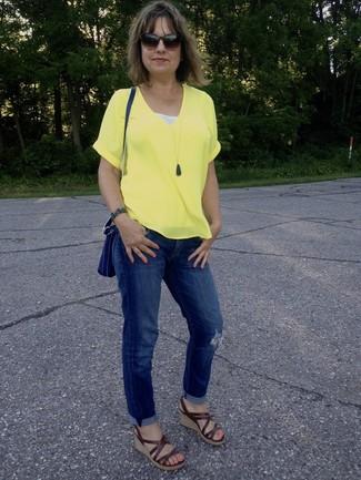 Cómo combinar: bolso bandolera de cuero azul, sandalias con cuña de cuero marrónes, vaqueros boyfriend desgastados azules, camiseta con cuello en v amarilla
