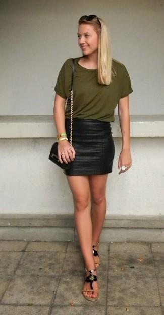 Cómo combinar: bolso bandolera de cuero negro, sandalias de dedo de cuero con adornos negras, minifalda de cuero negra, camiseta con cuello circular verde oliva