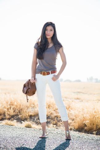 Cómo combinar: mochila con cordón de cuero marrón, sandalias de dedo de cuero doradas, vaqueros pitillo de encaje blancos, camiseta con cuello circular gris