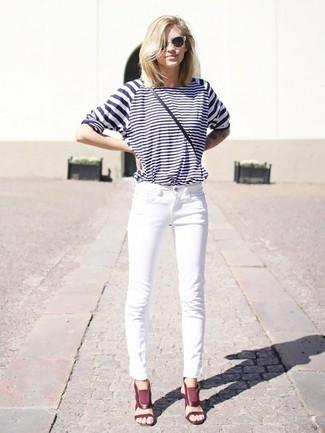 Cómo combinar: bolso bandolera de cuero negro, sandalias de tacón de cuero burdeos, vaqueros blancos, camiseta de manga larga de rayas horizontales en blanco y azul marino