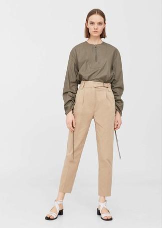 Cómo combinar: sandalias de tacón de cuero blancas, pantalón de pinzas marrón claro, blusa de manga larga verde oliva